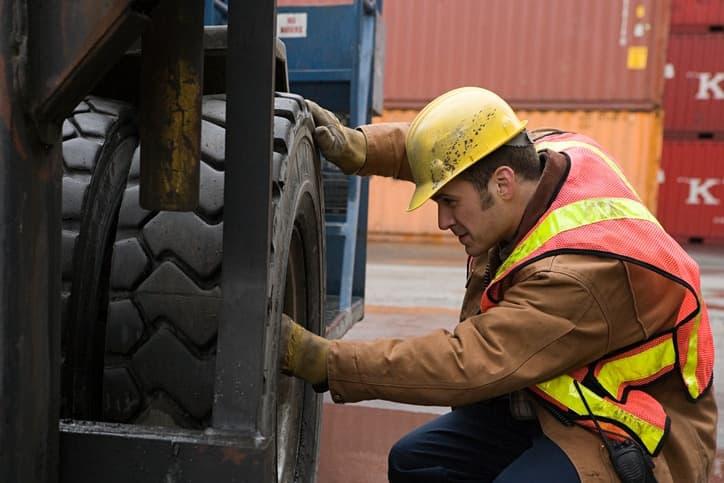 man inspecting tire
