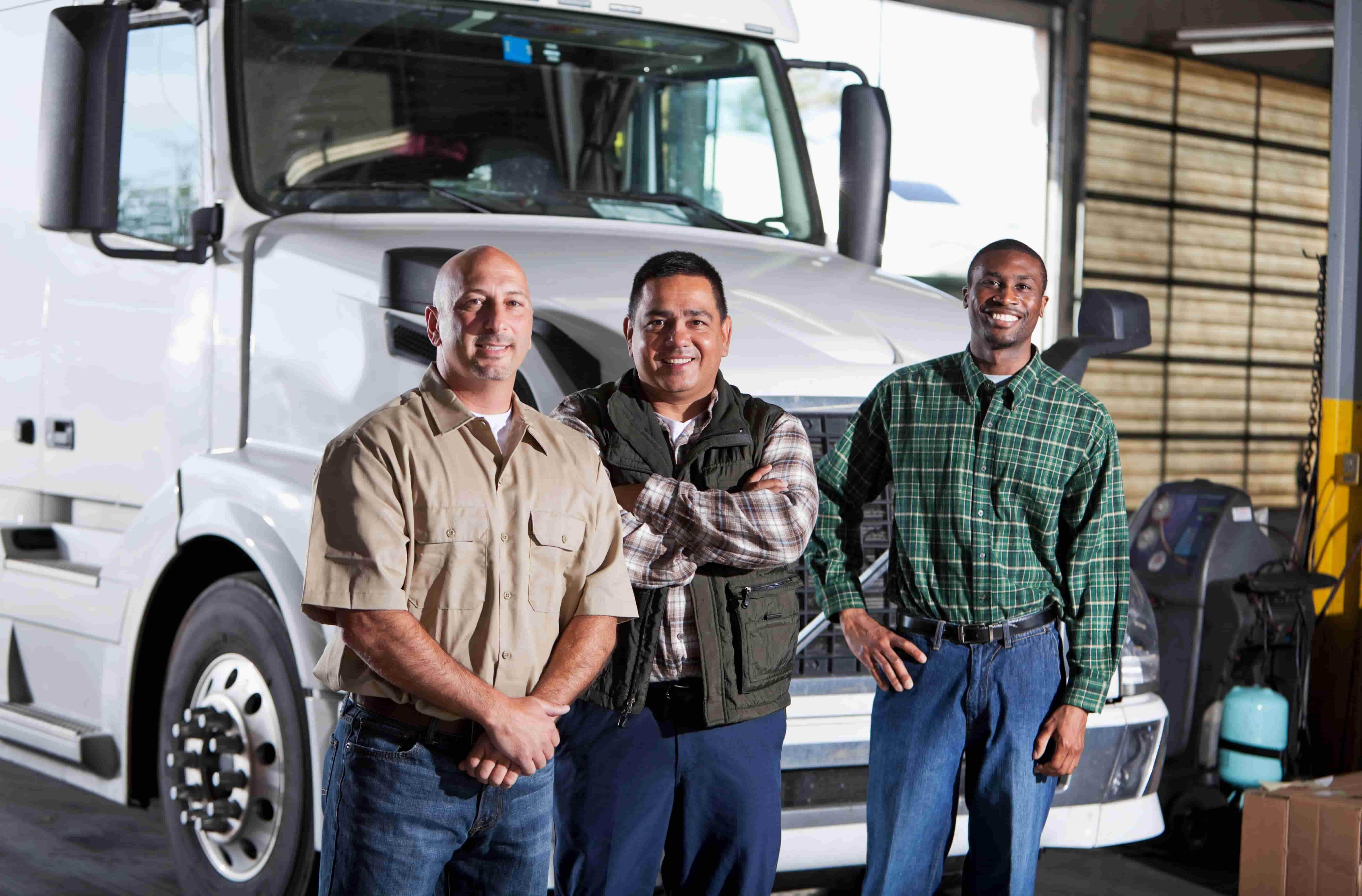 Three men standing by semi truck