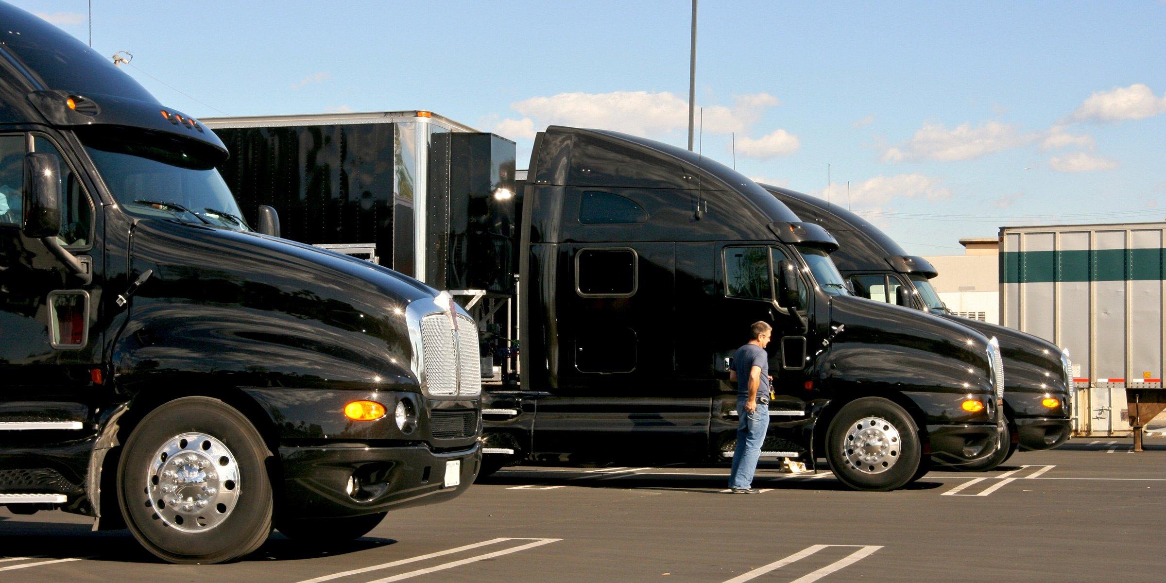 three black semi trucks