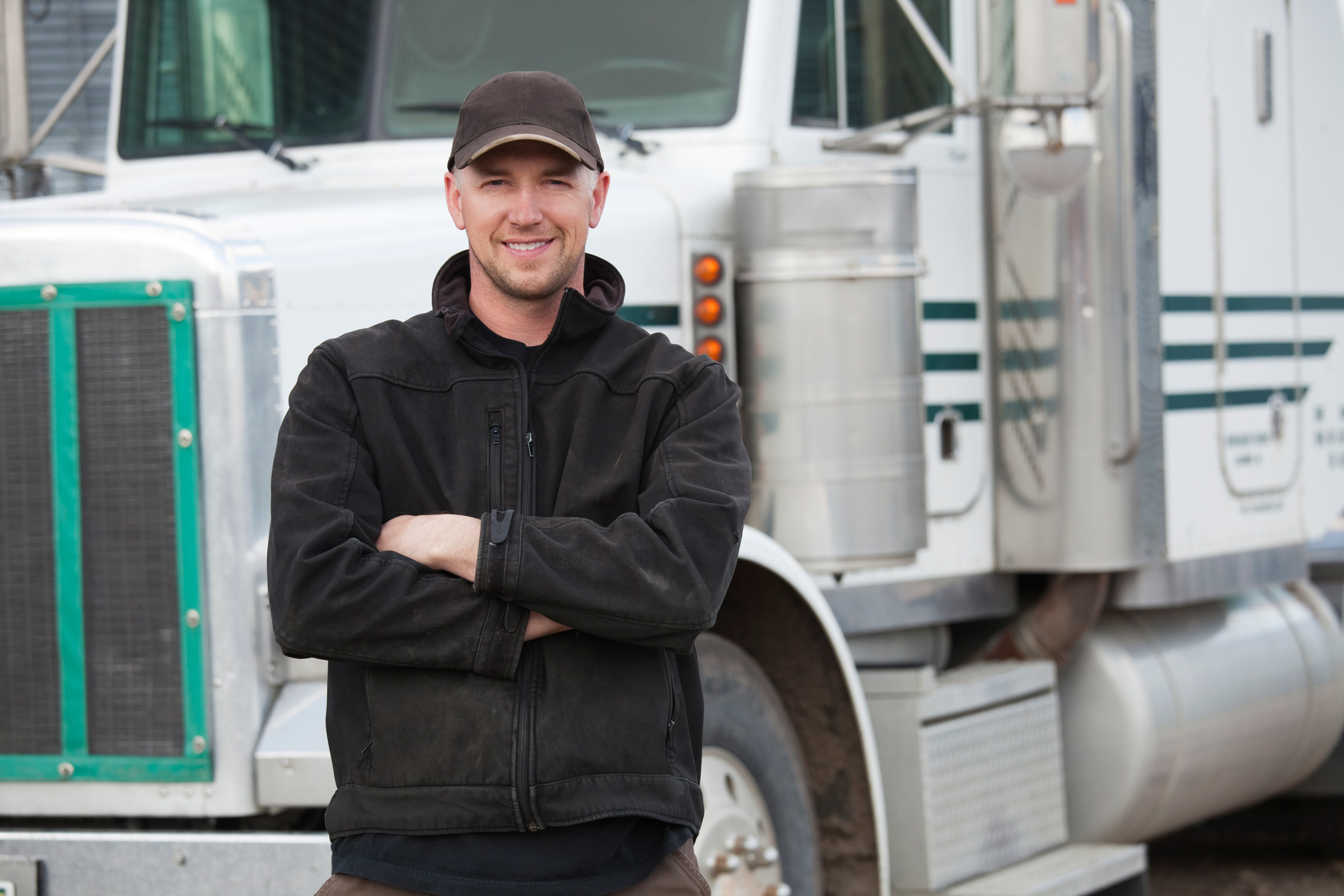 Male-truck-driver-standing-in-front-of-his-truck