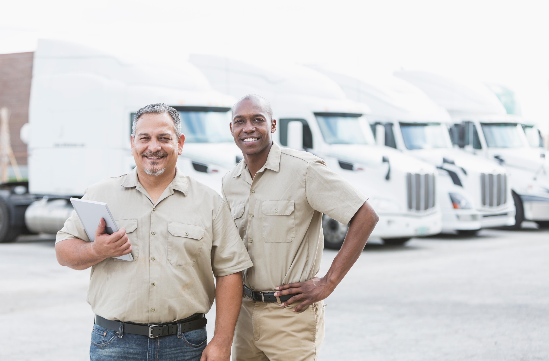Men standing by semi trucks